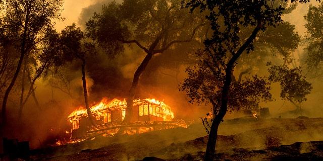 As chamas consomem uma cabana na vinícola da família Nichelini, no condado não incorporado de Napa, enquanto o incêndio de Hennessey arde na terça-feira, 18 de agosto de 2020.