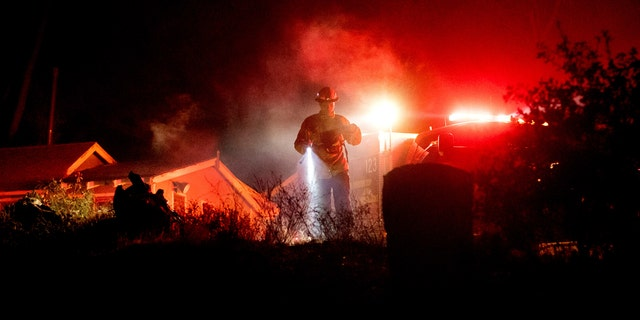Firefighter Capt. Kelvin Patterson extinguishes hot spots while protecting a home as the Lake Fire burns in the Angeles National Forest, Calif., north of Santa Clarita on Thursday, Aug. 13, 2020.