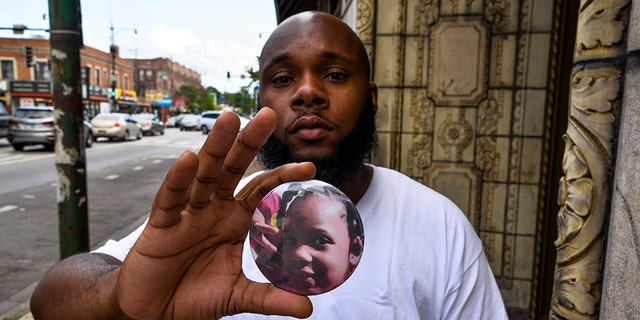 Nathan Wallace is standing in front of his house holding a button that shows his daughter Natalia Wallace in Chicago on Monday, August 3, 2020.  Natalia, 7, was killed on the west side of Chicago on July 4, 2020.  (AP Photo / Matt Marton)