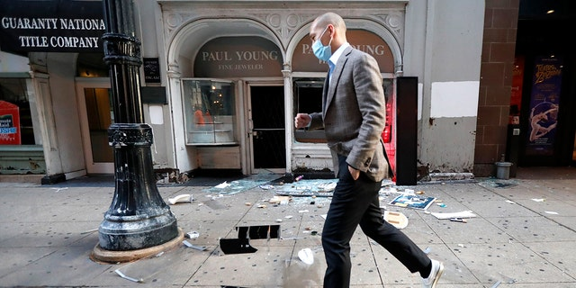 A pedestrian hops over debris Monday, Aug. 10, 2020, after a jewelry store was vandalized in Chicago's famed Loop. Chicago's police commissioner says more than 100 people were arrested following a night of looting and unrest that left several officers injured and caused damage in the city's upscale Magnificent Mile shopping district and other parts of the city.