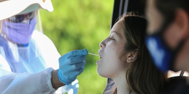 A health care worker gives a girl a throat swab test at a drive-in coronavirus (COVID-19) testing center at M.T.O. Shahmaghsoudi School of Islamic Sufism on Aug. 11, 2020, in Los Angeles, California. (Mario Tama/Getty Images)