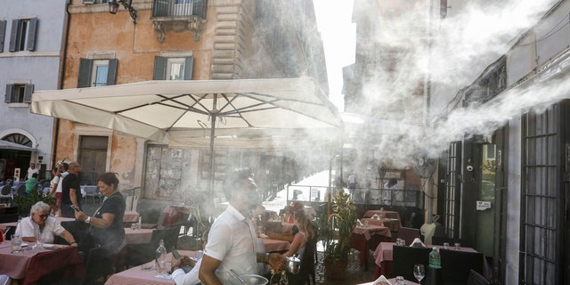 A fan sprays water as customers sit outside a cafe in downtown Rome, Friday, July 31, 2020.