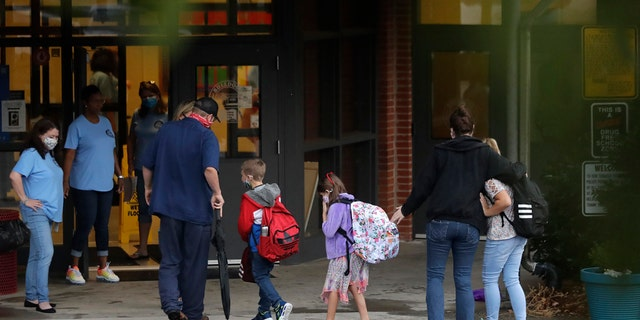 Students arrive at Dallas Elementary School in Dallas, Ga., for the first day of the 2020-21 school year amid the coronavirus outbreak. (AP Photo/Brynn Anderson)