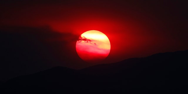 As wildfires burn throughout the Western Slope, the sun sets a bright orange behind the Rocky Mountains for residents of the eastern plains Wednesday, Aug. 12, 2020, in Denver.