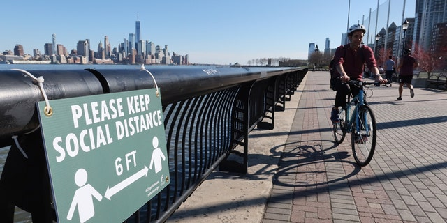 A cyclist rides past a newly installed sign encouraging social distancing to stop the spread of coronavirus along the Hudson River Walkway in Hoboken, N.J. (Photo by Gary Hershorn/Getty Images)