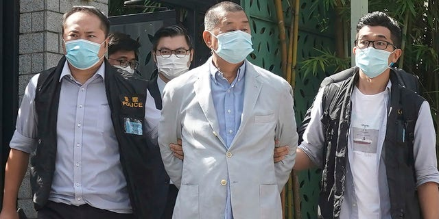 Lai, center, is arrested by police officers at his home in Hong Kong on Monday. (AP Photo)