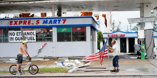 Dustin Amos, right, walks near debris at a gas station on Thursday, Aug. 27, 2020, in Lake Charles, La., after Hurricane Laura moved through the state.