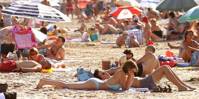 Beachgoers sunbathe at Cap d'Agde, France along the Mediterranean Sea.