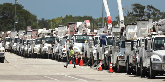 Dozens of utility trucks are lined up to be processed by Florida Power & Light at Daytona International Speedway on Saturday, Aug. 1, 2020.