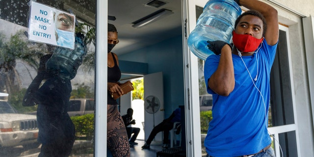 A man carries drinking water for a customer at a water depot store before the arrival of Hurricane Isaias in Freeport, Grand Bahama, Bahamas, Friday, July 31, 2020.