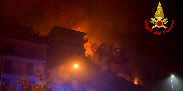 Flames burn behind buildings in the town of Altofonte, near the Sicilian city of Palermo, southern Italy, Saturday, Aug. 29, 2020.