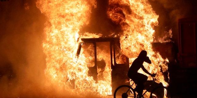 A man on a bike rides past a city truck on fire outside the Kenosha County Courthouse in Kenosha, Wis., on Aug. 23, 2020. (Mike De Sisti/Milwaukee Journal Sentinel via USA TODAY via REUTERS)