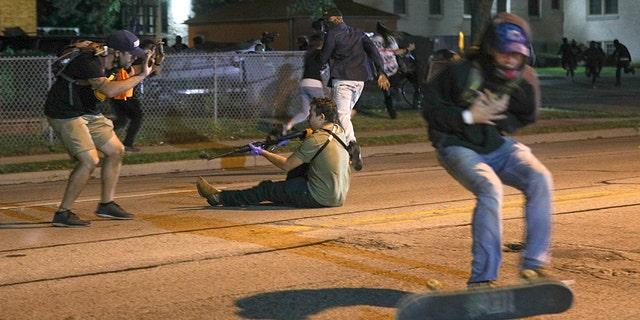 A man (to the right in this photo) was shot in the chest as fighting erupted on the streets of Kenosha on Tuesday night.