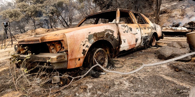 A burned vehicle rests along Pine Canyon Road as the Lake Fire burns in the Angeles National Forest. (AP)