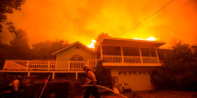 Firefighters work near a home as the Lake Fire burns in the background on Wednesday. (AP)