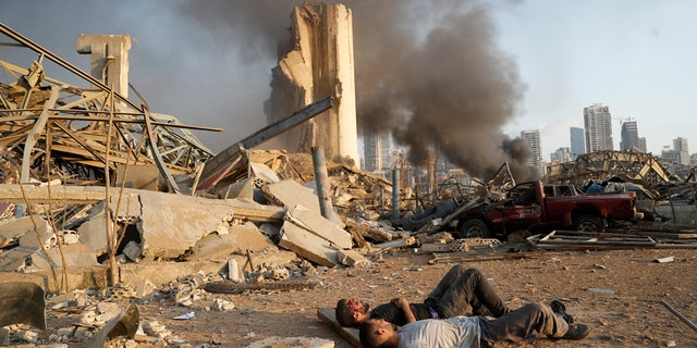 Two injured men lie on the ground, waiting for help at the explosion scene that hit the seaport, in Beirut Lebanon, Tuesday, Aug. 4, 2020. (AP Photo/Hussein Malla)