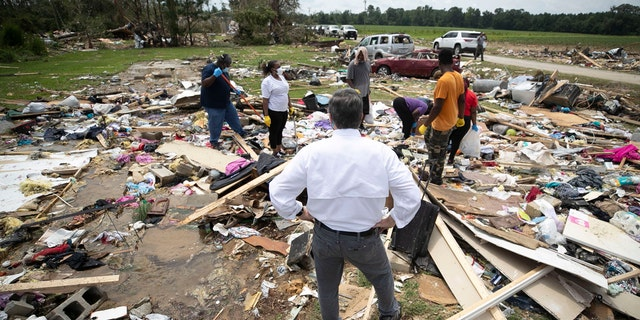 North Carolina Gov. Roy Cooper talks with residents, Wednesday, Aug. 5, 2020, as they looks for personal items in the rubble after a tornado spawned by Hurricane Isaias destroyed a rural mobile home neighborhood killing two residents near Windsor N.C.