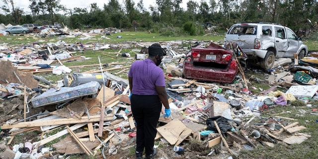 Cynthia Cooper looks for personal items for a family member who had their home destroyed after a tornado spawned by Hurricane Isaias destroyed a rural mobile home neighborhood killing two residents near Windsor N.C. on Wednesday, Aug. 5, 2020.