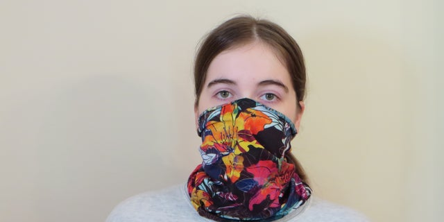 Emma Fischer, study co-author and student at Duke University, dons a neck gaiter. Study co-author Warren S. Warren says this neck gaiter is slightly stretchy and opaque when worn, but single layer and thin enough to see a light through it. (Photo Credit: Martin Fischer, Duke University)