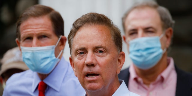 Connecticut Gov. Ned Lamont, center, signed the order approving the new fines for failing to violate the state's coronavirus mask order.