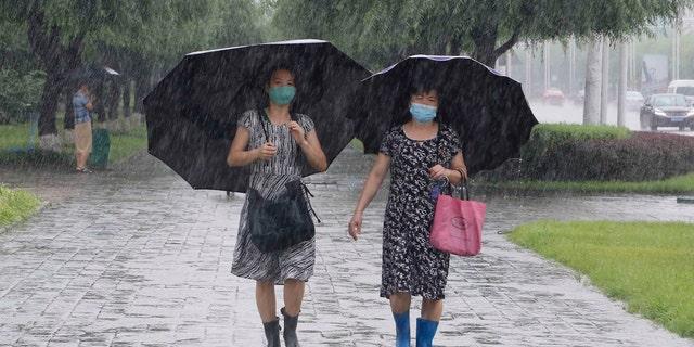 Women walk with umbrellas during torrential rains, Wednesday, August 5, 2020, in Pyongyang.