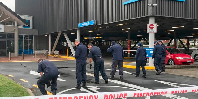 Police search outside the Chartwell Shopping Centre in Hamilton, New Zealand, on Thursday after would-be thieves tried to detonate pipe bombs outside an ATM. (Belinda Feek/NZ Herald via AP)