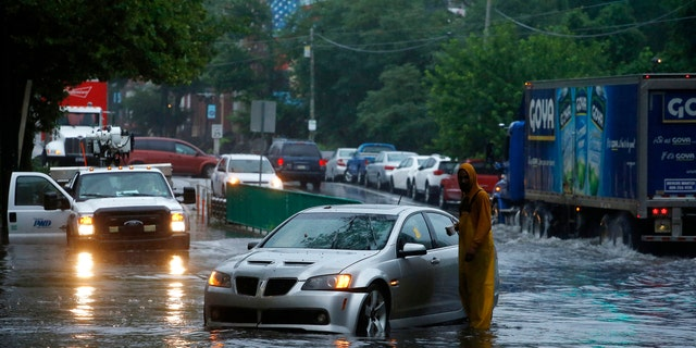 A man checks on a stranded vehicle during Tropical Storm Isaias, Tuesday, Aug. 4, 2020, in Philadelphia. The storm spawned tornadoes and dumped rain during an inland march up the U.S. East Coast after making landfall as a hurricane along the North Carolina coast. (AP Photo/Matt Slocum)