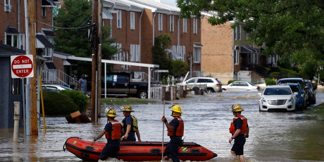 Philadelphia firefighters walk through a flooded neighborhood after Tropical Storm Isaias moved through, Tuesday, Aug. 4, 2020, in Philadelphia.