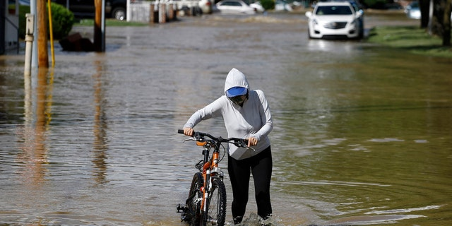 A woman pushes a bike through a flooded neighborhood during Tropical Storm Isaias, Tuesday, Aug. 4, 2020, in Philadelphia.