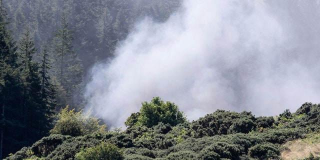 Smoke billows from the scene of a derailed train in Stonehaven, Scotland, Wednesday Aug. 12, 2020. (Derek Ironside/Newsline-media via AP)