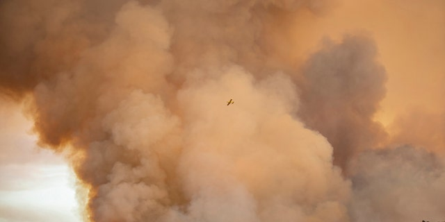 A hydroplane flies over a wildfire in Almonaster la Real in Huelva, Spain, Thursday Aug. 27, 2020.