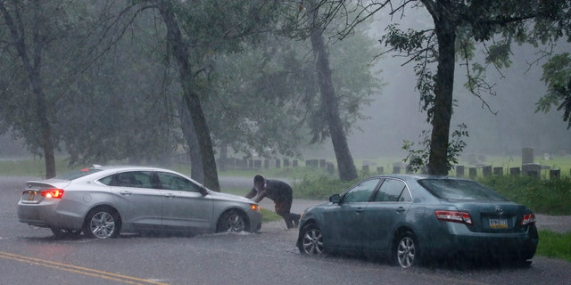 A man pushes a car through a flooded street during Tropical Storm Isaias, Aug. 4, in Philadelphia.