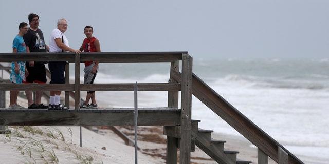 Beach goers watch waves churned up by Tropical Storm Isaias near Jaycee Beach Park, Sunday, Aug. 2, 2020, in Vero Beach, Fla.