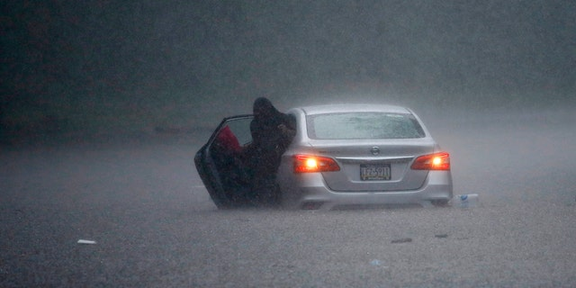 A woman claims out of a stranded car during Tropical Storm Isaias, Aug. 4, in Philadelphia.