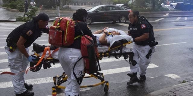 A person who was injured while trying to secure barriers meant to block flood waters at a building at Water and State Streets in lower Manhattan is transported after being injured Tuesday, Aug. 4, 2020, in New York.