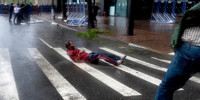 A person lays on a crosswalk after being knocked to the street by wind in lower Manhattan Tuesday, Aug. 4, 2020, as Tropical Storm Isaias produced strong winds as the storm moved past, at times causing damage.