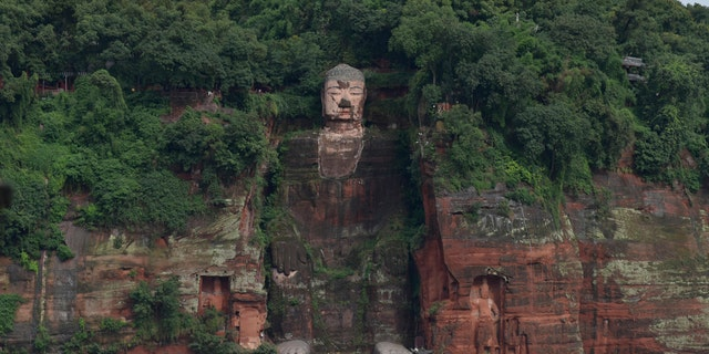 In this photo released by China's Xinhua News Agency, floodwaters flow near the historic Giant Buddha in Leshan in southwestern China's Sichuan Province on Aug. 18, 2020.