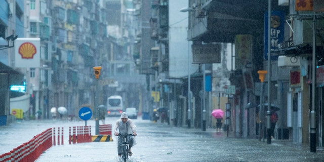 In this photo released by China's Xinhua News Agency, a man rides a bicycle during a rainstorm in Macao, Wednesday, Aug. 19, 2020.