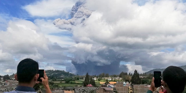 Indonesian men use their mobile phones to take photos as Mount Sinabung spews volcanic materials into the air as it erupts, in Karo, North Sumatra, Indonesia, Monday, Aug. 10, 2020.