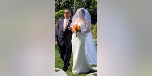 August bride Narolin Cepeda was able to wear her recovered wedding dress earlier this month after the TSA found her forgotten dress in Newark. She was escorted down the aisle by her father, Marino. (Christopher Cepeda)