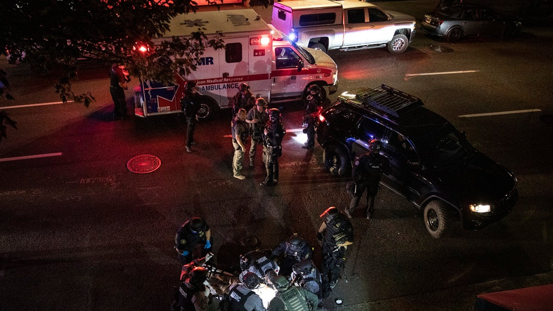 """A man late identified as 39-year-old Aaron """"Jay"""" Danielson is treated after being shot in Portland, Ore., before succumbing to his wounds later. (AP Photo/Paula Bronstein)"""