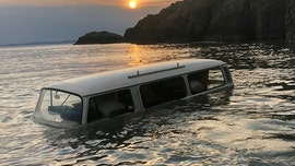 Classic VW Microbus submerged on beach during high tide