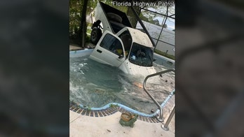 Truck swerves off a road through patio, before landing in backyard swimming pool