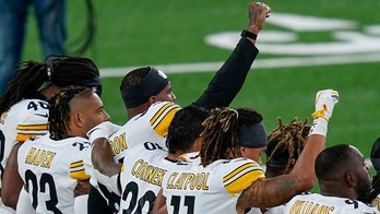 Steelers players stand for national anthem, hold banner before game vs. Giants
