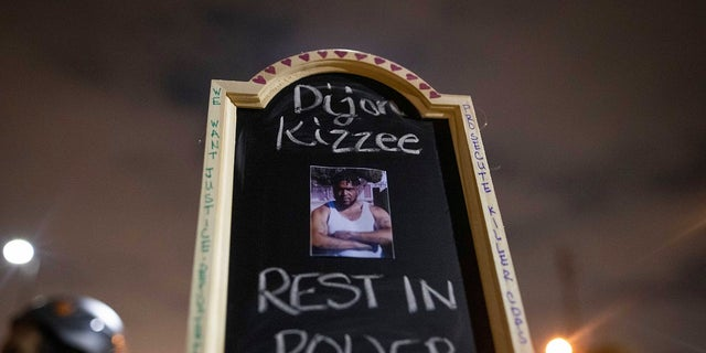 A protester holds a sign with a picture of Dijon Kizzee, a Black man who died after being shot by deputies of the Los Angeles Sheriff's Department on Monday in Los Angeles. (AP Photo/Christian Monterrosa)