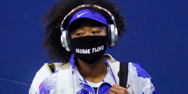 """Naomi Osaka of Japan wears a protective mask due to the COVID-19 virus outbreak, featuring the name """"George Floyd,"""" while arriving on court to face Shelby Rogers of the United States during the quarterfinal round of the US Open tennis championships, Tuesday, Sept. 8, 2020, in New York. (AP Photo/Frank Franklin II)"""