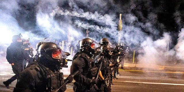 Police use chemical irritants and crowd control munitions to disperse protesters during the 100th consecutive day of demonstrations in Portland, Ore., on Saturday, Sept. 5, 2020. AP Photo/Noah Berger)