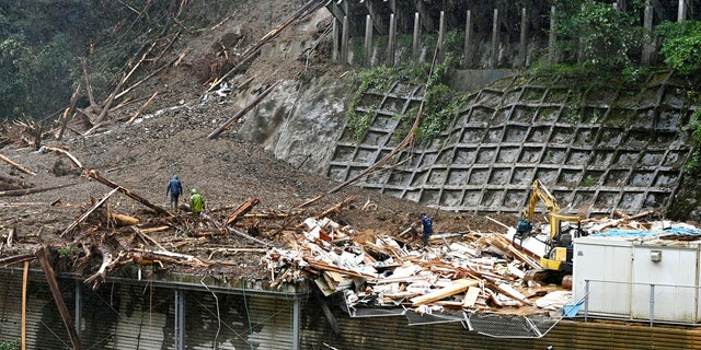 Rescuers work at a landslide site as a typhoon hit Shiiba village, Miyazaki prefecture, southwestern Japan Monday, Sept. 7, 2020.