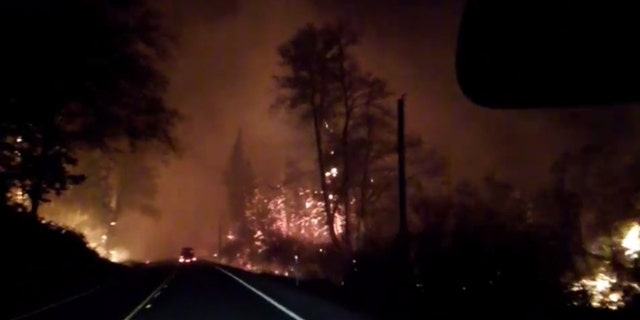 Flames can be seen Oregon Highway 18 in Lincoln County on Sept. 9, 2020 are residents evacuate from wildfires in the area.