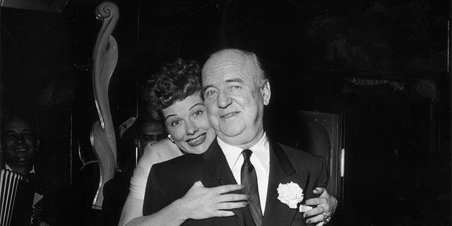 Circa 1953: American actor Lucille Ball (1911-1989) hugs American actor William Frawley (1887-1966) as she stands behind him during the surprise party for her 13th wedding anniversary to Desi Arnaz, held at Larry Finley's restaurant on Sunset Strip, Los Angeles, Calif.